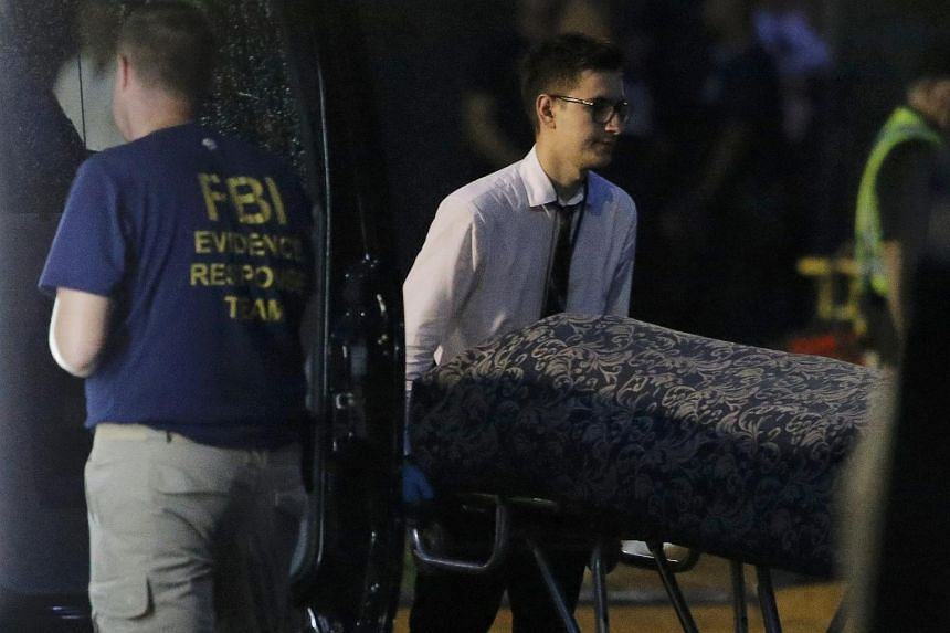 Police forensic investigators work at the crime scene of a mass shooting, as bodies are removed at the Pulse gay nightclub in Orlando on June 12.