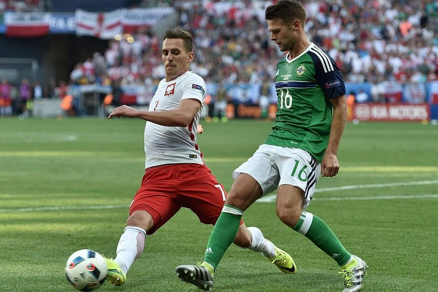 Arkadiusz Milik (left) of Poland and Oliver Norwood of Northern Ireland in action during the Euro 2016 group C match between Poland and Northern Ireland.