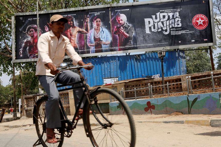 A man rides his bicycle past a poster of the movie Udta Punjab in Mumbai, India, on June 13, 2016.