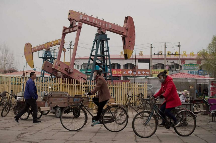 Local residents riding bicycles next to oil pumps in Daqing, China.