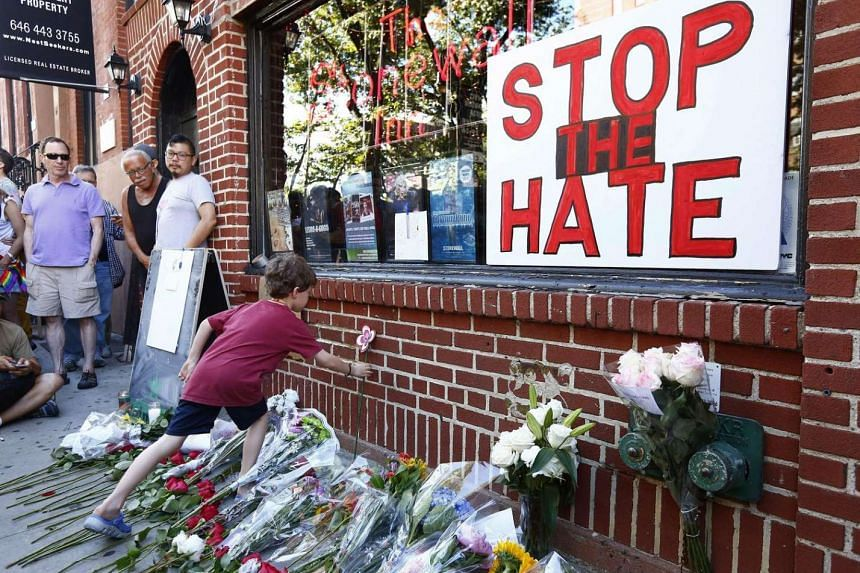 Nicolas Brown-Spino sets down a paper flower at a make-shift memorial in front of the Stonewall Inn as people gather for a vigil following the massacre that occurred at a nightclub in Orlando.