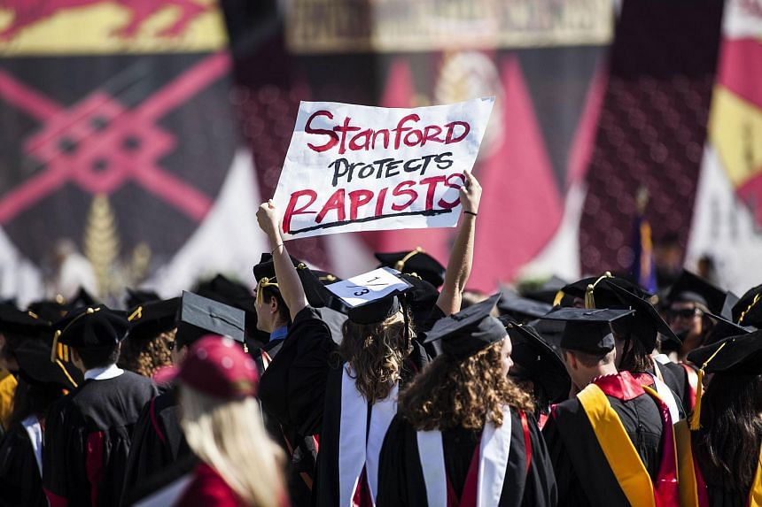 A graduating student holds a sign in protest during the Wacky Walk before the 125th Stanford University commencement ceremony on June 12 in Stanford, California.