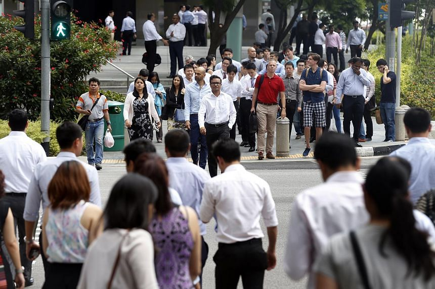 Office workers crossing the junction at Raffles Quay in Singapore on Feb 18, 2015.