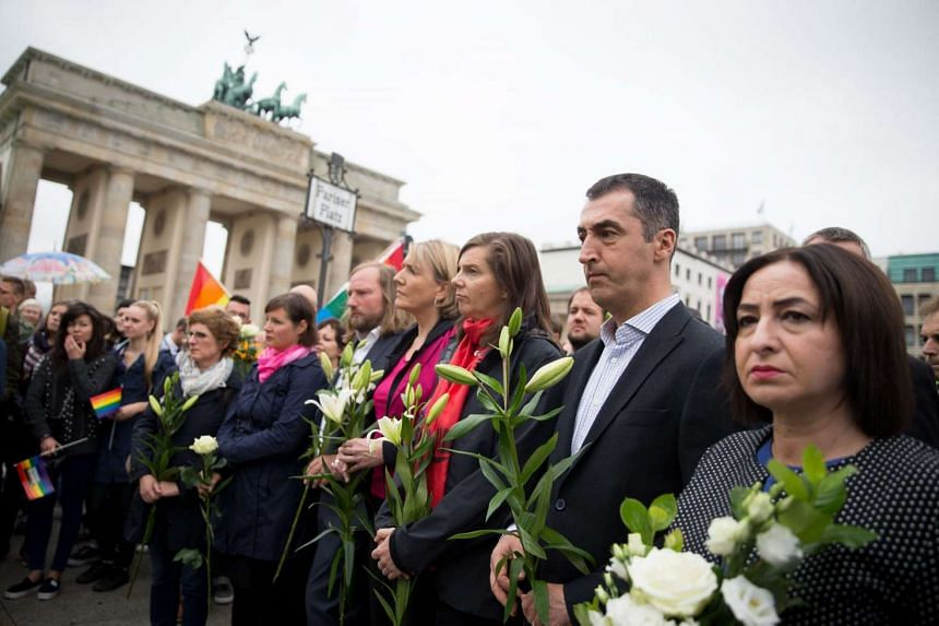 People attending a memorial for the victims of a mass shooting at an Orlando gay nightclub, at the US embassy, in front of Brandenburg Gate, Berlin, Germany, on June 13, 2016.