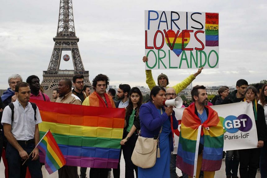A man holding a sign near people waving rainbow flags as they gather on the Parvis des droits de l'homme near the Eiffel Tower in Paris on June 13, 2016 to pay homage to the victims of a shooting at a gay nighclub in Orlando.