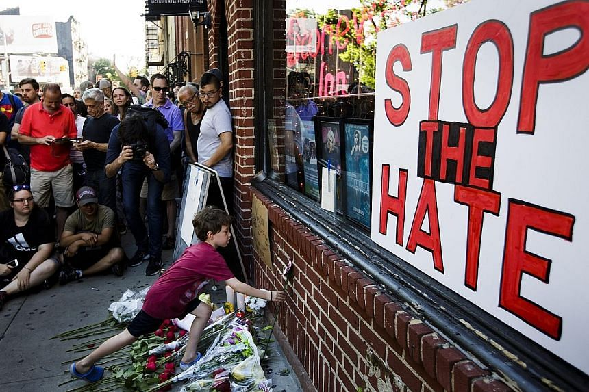 A boy in New York paying tribute to the victims of Sunday's mass shooting in an Orlando club, in which 49 people were killed. Although the gunman pledged allegiance to ISIS during a 911 call, US officials said it was too early to tell if he had any c