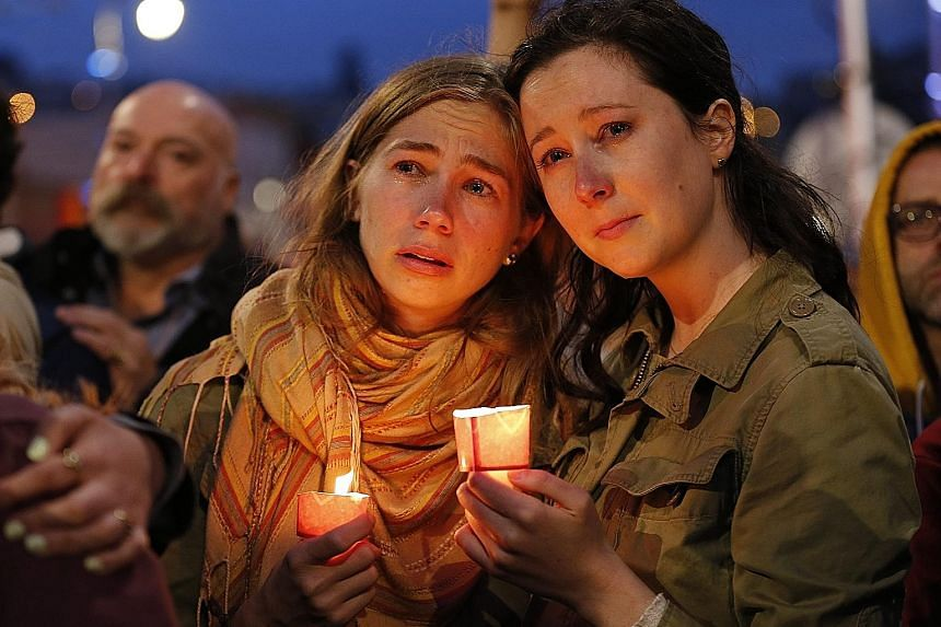 Mourners at a vigil to remember the victims at Harvey Milk Plaza in San Francisco's Castro District on Sunday. Forty-nine people were killed in the deadliest mass shooting in US history. People gathering in shock and grief (above) in the streets near