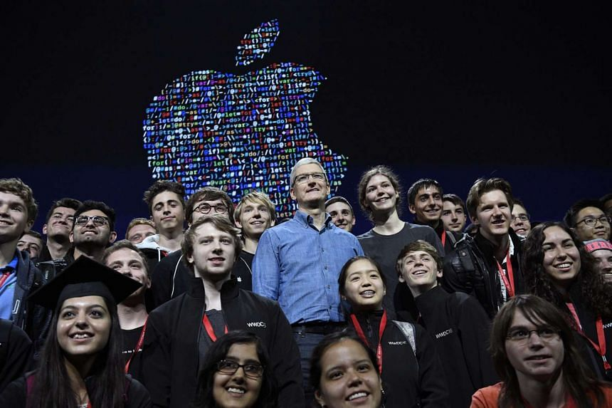 Chief executive officer of Apple Inc., Tim Cook (center) stands for a photograph with WWDC 2016 Scholarship programme winners during the Apple WWDC in San Francisco, California, US, on June 13.