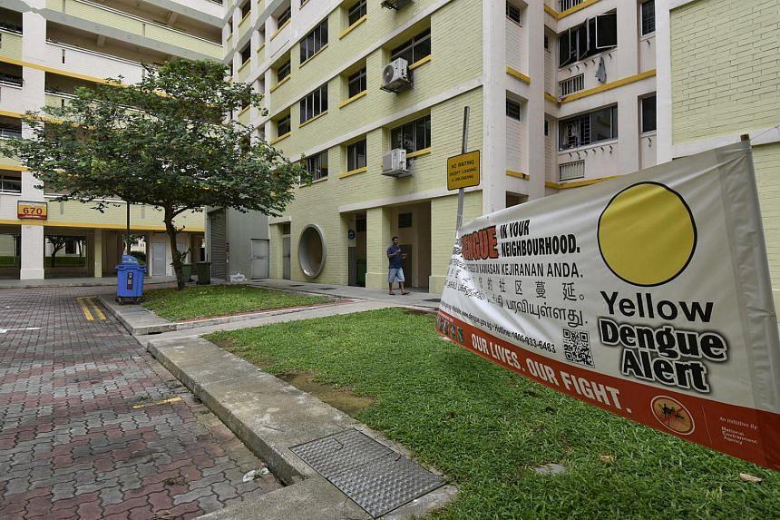 A yellow dengue alert banner in front of Block 670 in Jalan Damai.