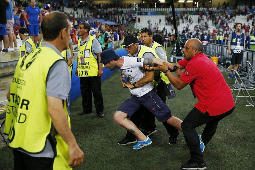 A fan is restrained by security after the game between England v Russia on Saturday (June 11).