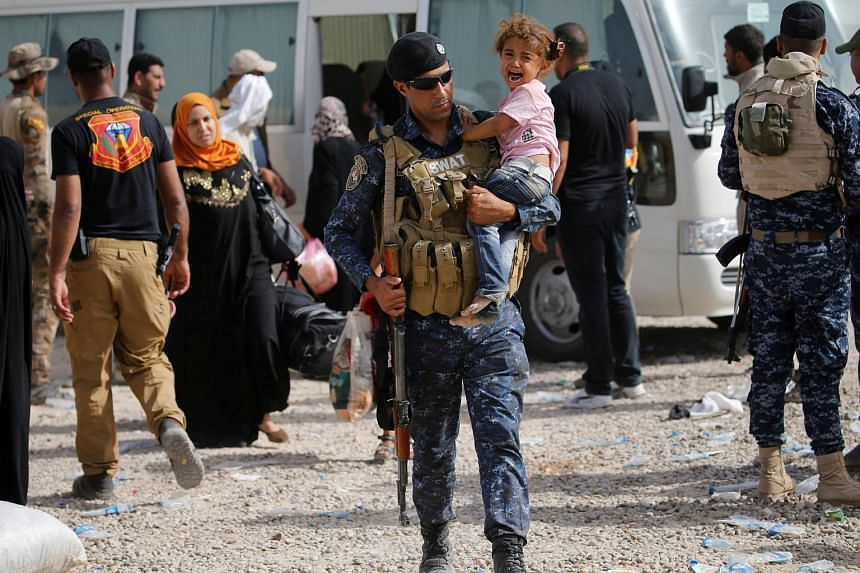 A member of the Iraqi security forces carries a child as he assists civilians, who had fled their homes due to clashes, at Camp Tariq, south of Falluja, Iraq, June 4.