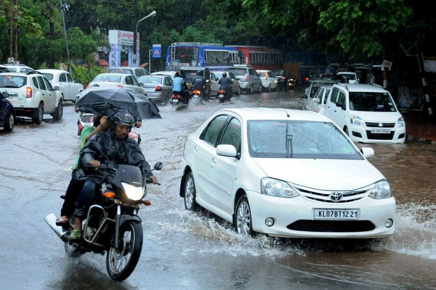 Indian commuters make their way along a waterlogged road during heavy monsoon rains in Kochi, on June 8, 2016.