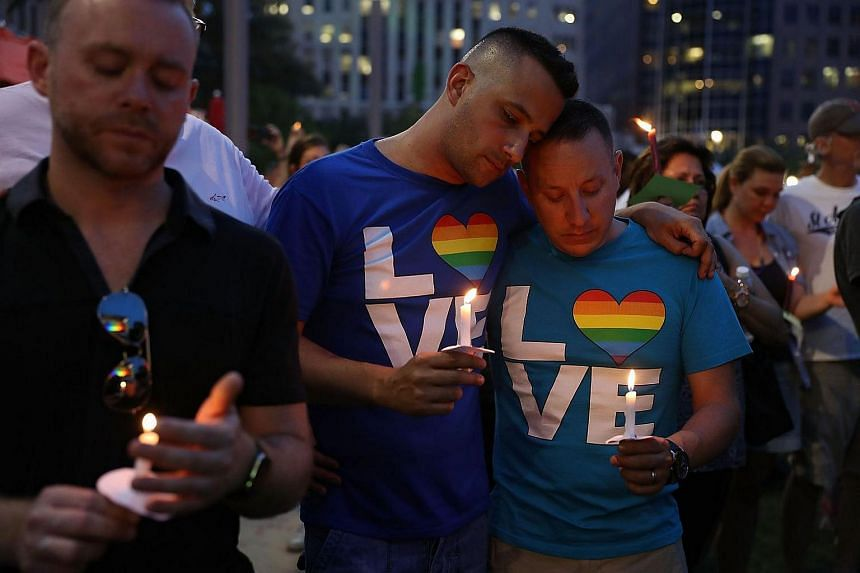 People holding candles during a memorial service at the Dr Phillips Centre for the Performing Arts in Orlando, Florida.