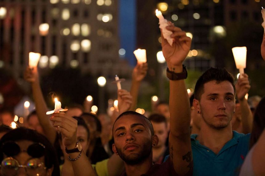 People hold candles during a memorial service for the victims of the Pulse Nightclub shootings, at the Dr. Phillips Centre for the Performing Arts, on June 13, 2016 in Orlando, Florida.