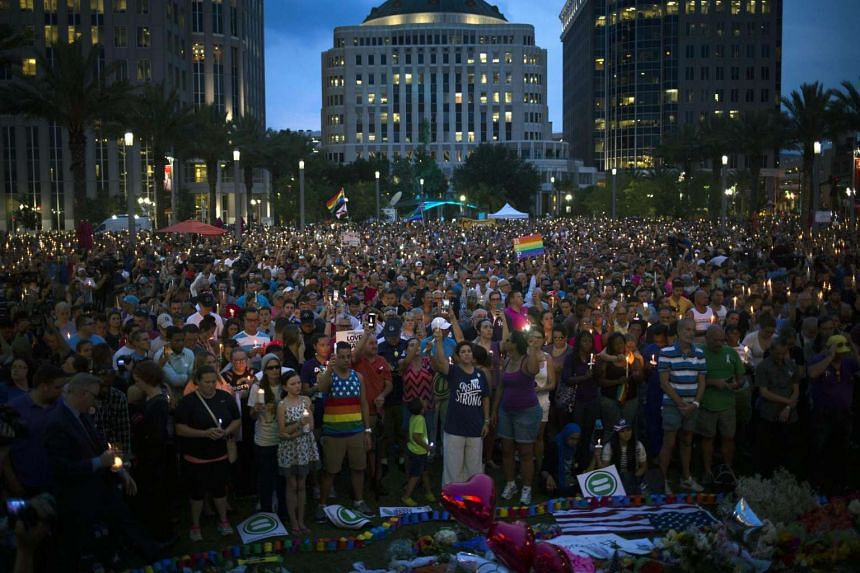Hundreds of people gather at a candle light vigil outside of the Dr. Phillips Centre for the Performing Arts to place tributes and flowers in honour to the victims of a mass shooting, in Downtown, Orlando, Florida, on June 13, 2016.