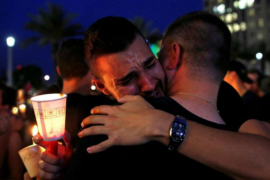 People embrace during a candlelight vigil at a memorial service for the victims of the shooting at the Pulse gay night club in Orlando, Florida, on June 13, 2016.