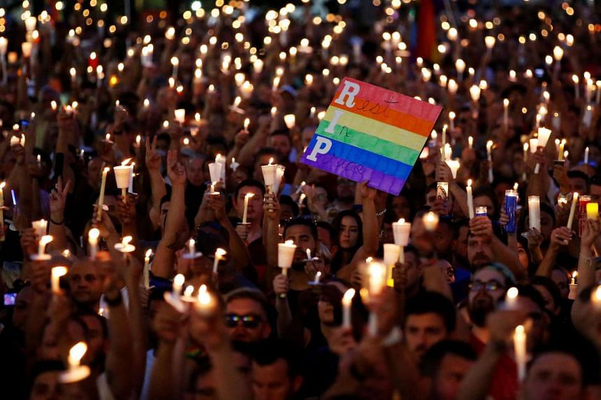 People take part in a candlelight memorial service the day after a mass shooting at the Pulse gay nightclub in Orlando, Florida, on June 13, 2016.