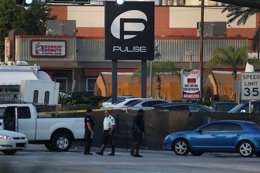 Law enforcement officials investigate near the Pulse Nightclub on June 13 in Orlando, Florida.