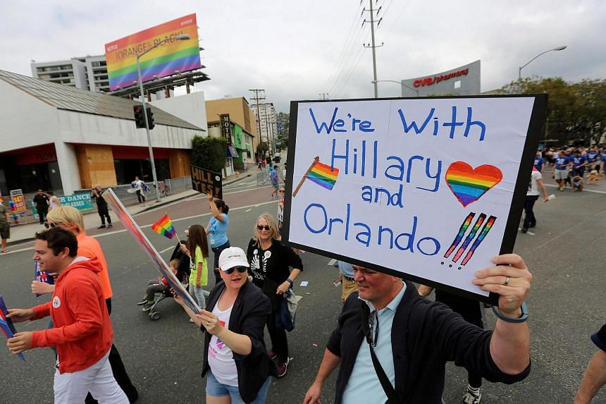 A man carrying a sign supporting both the Orlando shooting victims and Democratic presidential candidate Hillary Clinton at the 46th annual Los Angeles Gay Pride Parade, following the shooting at a nightclub in Orlando.