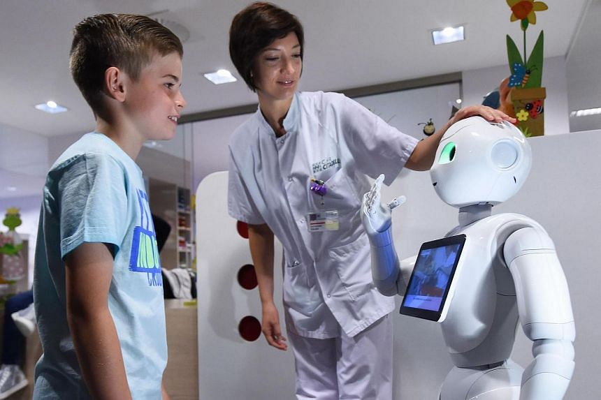A boy speaking with Pepper the robot next to a nurse during a press conference at the Centre Hospitalier Regional La Citadelle in Liege on June 13.