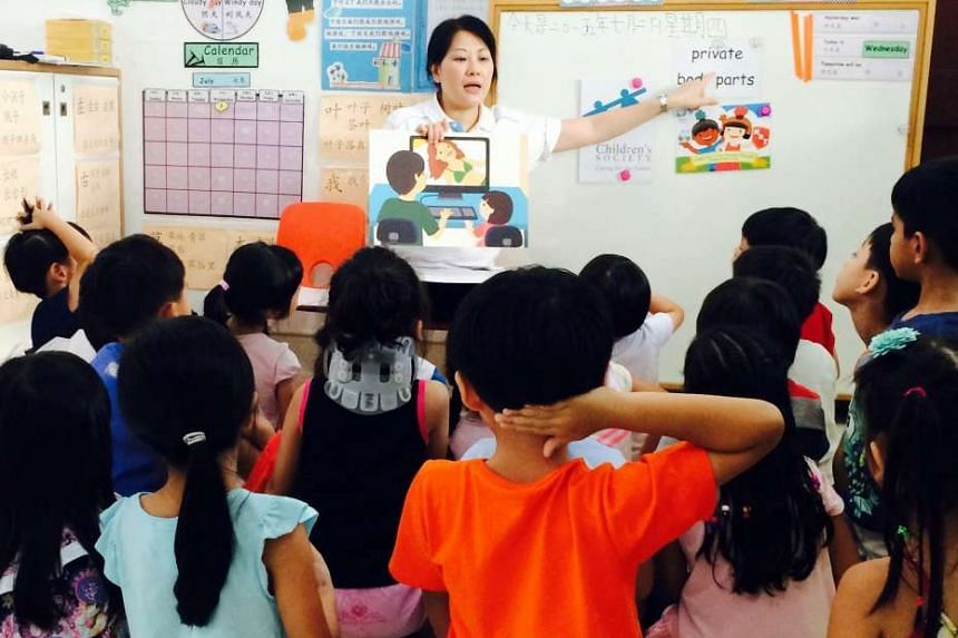 """A staff member of Singapore Children's Society conducting a KidzLive session to teach five- and six-year-olds """"body safety"""" skills."""