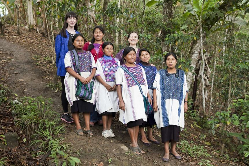Carla Fernandez (background, far right, with artisans from Mexico) has spent the past 20 years working with people from indigenous communities for her contemporary and avant-garde fashion designs.