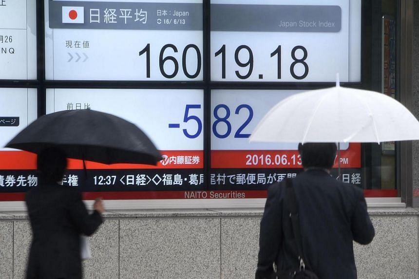 Pedestrians walk past the electronic market indicator showing Tokyo stock market price in Tokyo on June 13.
