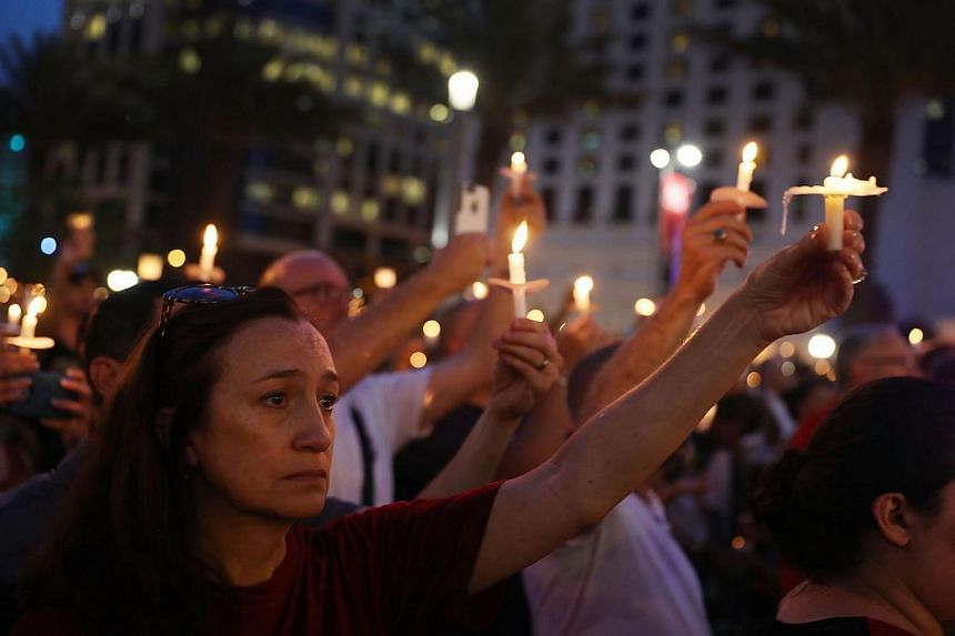 People hold candles during a memorial service for the mass shooting victims at the Pulse nightclub on June 13 in Orlando.