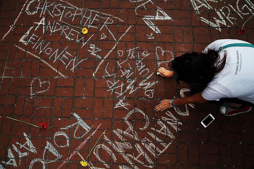 A woman pauses while writing the names of shooting victims in chalk in a park across The Stonewall Inn in New York City.