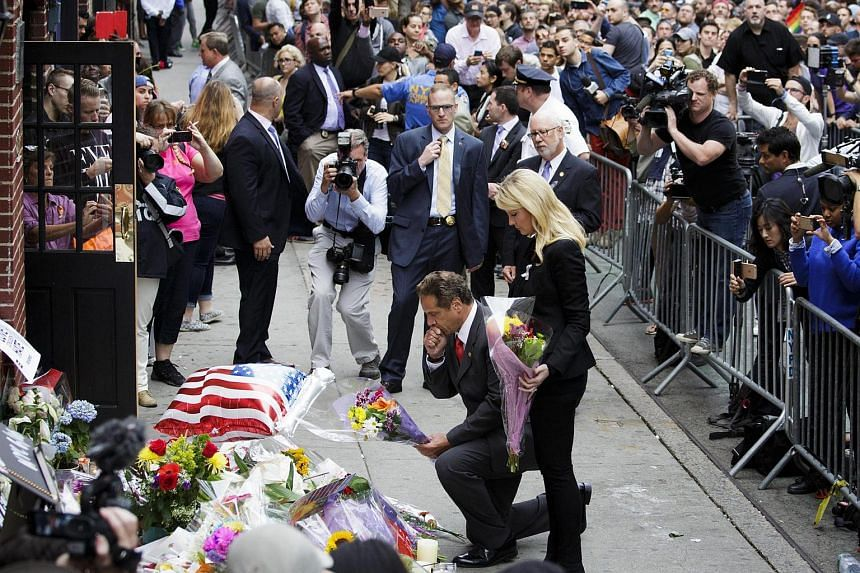 New York Governor Andrew Cuomo (centre, front) places flowers at a memorial for the victims killed in the mass shooting at Pulse nightclub.