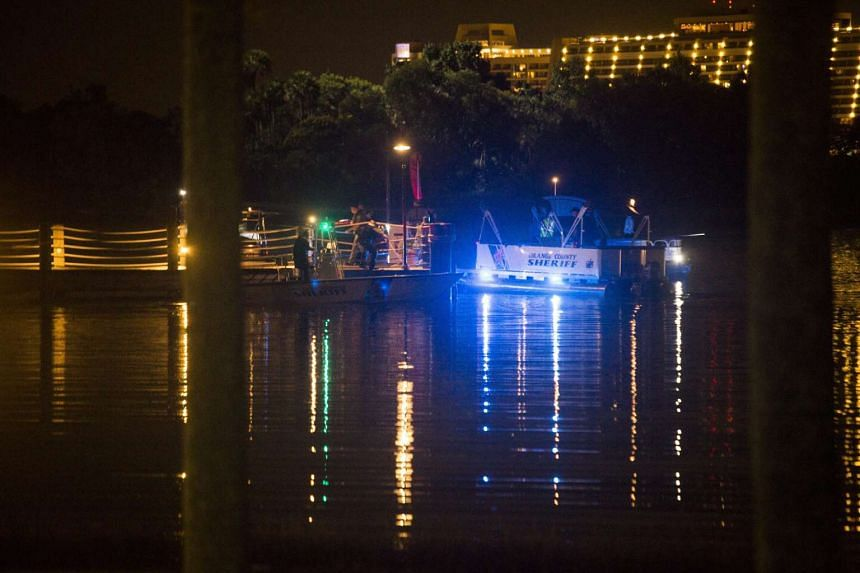 Police officers search for a child who was reportedly pulled into the water by an alligator near Disney's Grand Floridian Resort & Spa in Orlando, Florida on June 14, 2016.