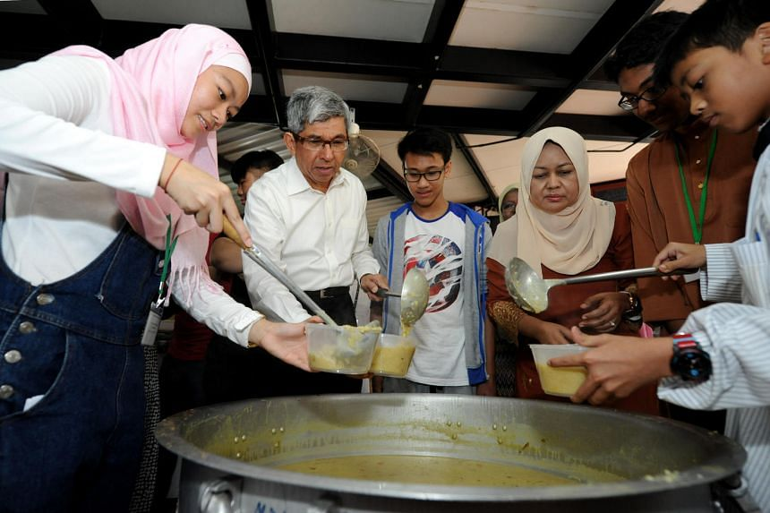 Dr Yaacob Ibrahim, Minister of Communications and Information and Minister-in-Charge of Muslim Affairs, preparing the bubur with youths from the Entrepreneurship, Leadership and Lifeskills for Youth @SENSE Programme at Masjid Darul Aman.