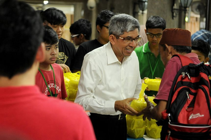 Dr Yaacob Ibrahim, Minister of Communications and Information and Minister-in-Charge of Muslim Affairs, distributing the bubur to worshippers at Masjid Darul Aman.