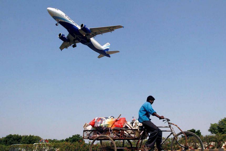 An IndiGo Airlines aircraft prepares to land as a man paddles his cycle rickshaw in Ahmedabad, India on October 26, 2015.