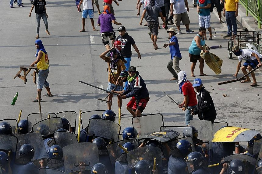 Filipino informal settlers clashing with anti-riot police yesterday during a demolition of shanties in Quezon city in the east of Manila in the Philippines. According to local news reports, scores were hurt during the stand-off, including members of