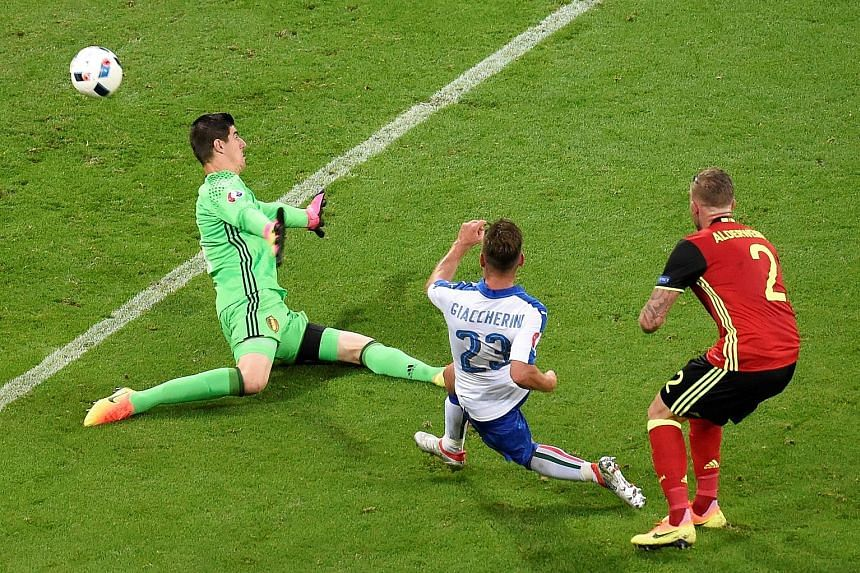 Italy midfielder Emanuele Giaccherini shooting the Azzurri's first goal past Belgium goalkeeper Thibaut Courtois. Belgium were highly rated before the game but flattered to deceive.
