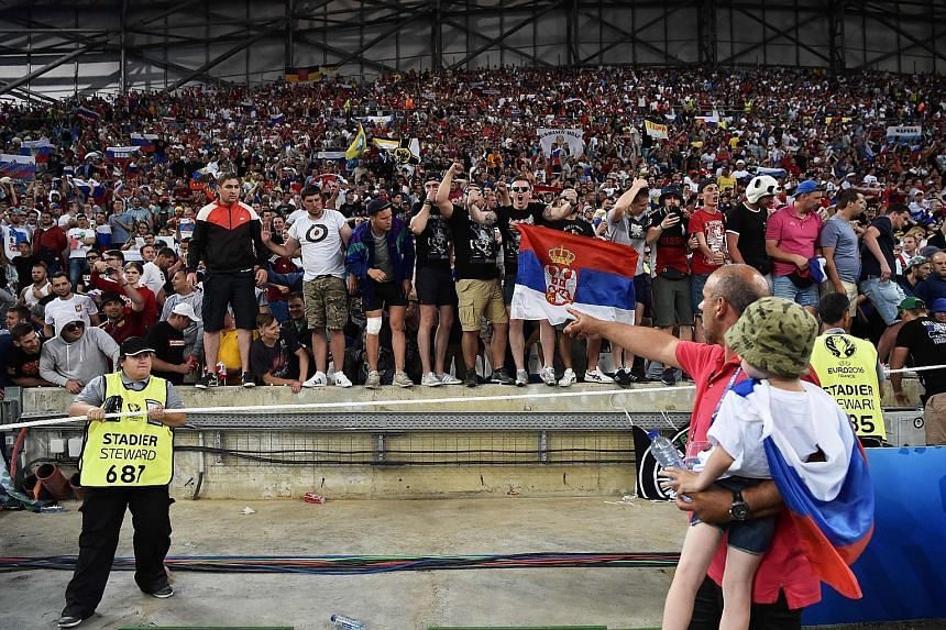 Russian supporters, some brandishing a Serbian flag, chanting before the 1-1 draw against England last Saturday. Russia will be expelled if there is more crowd trouble.
