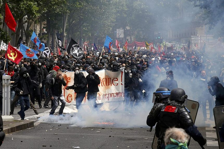Demonstrators wearing masks clashing with police in Paris yesterday. At least 26 people were injured and 15 arrested as tens of thousands of people rallied against the planned labour law reforms that would make hiring and firing easier.