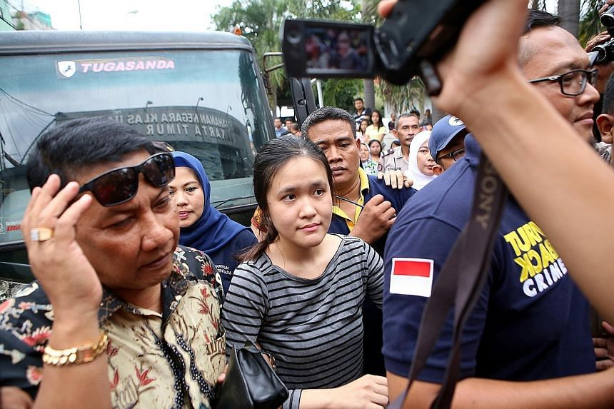 Jessica surrounded by officials as she arrived at the Pondok Bambu Women's Detention Centre in East Jakarta on May 27. The murder suspect allegedly laced her friend's iced coffee with cyanide at a cafe.