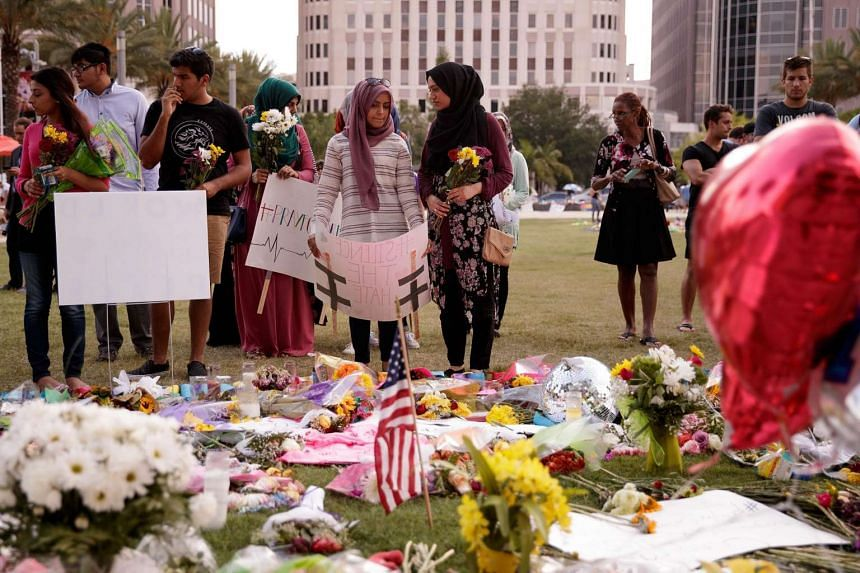 Young people from Husseini Islamic Centre in Sanford, Florida, visit a makeshift memorial at the Dr. Phillips Centre for Performing Arts in Orlando, Florida.