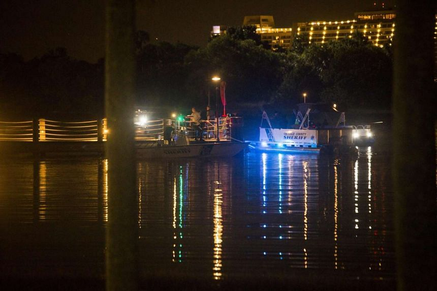 Police officers searching for a child who was pulled into the water by an alligator in Orlando, Florida.