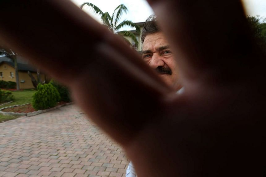 Seddique Mateen, father of Omar Mateen, grabs a photographer's lens at his home in Port Saint Lucie, Florida,  June 14, 2016.