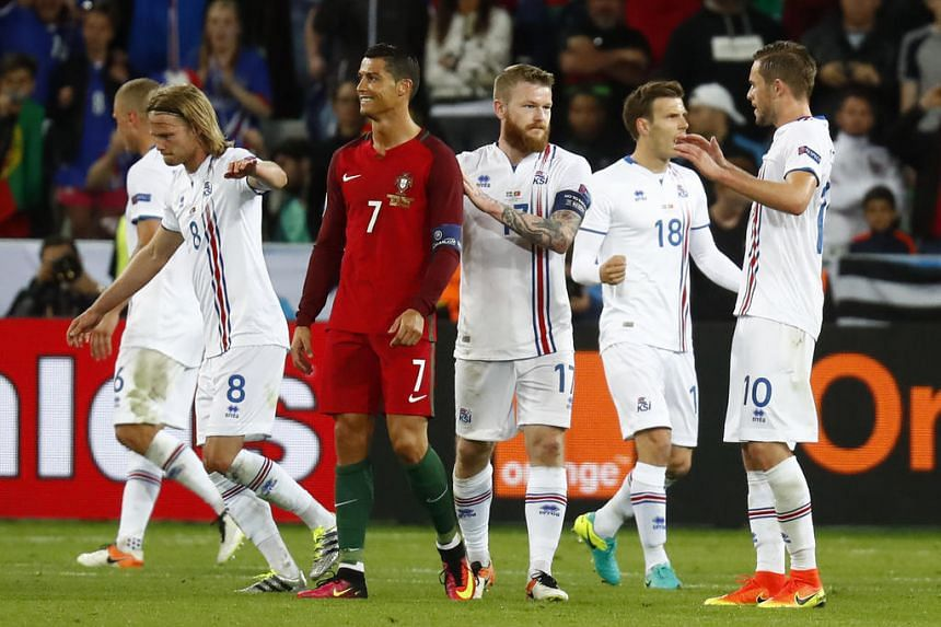 Cristiano Ronaldo (in red) after the end of the match, as Iceland players celebrate.