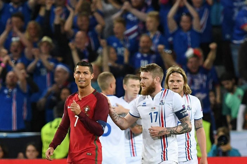 Iceland's Aron Gunnarsson (right) with Cristiano Ronaldo after the draw.
