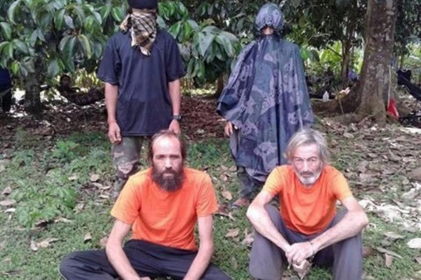 Hostages Canadian Robert Hall (front, right) and Norwegian Kjartan Sekkingstad in an undated picture released to local media, in Jolo island, southern Philippines.