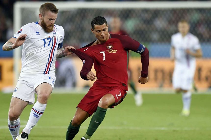 Iceland's midfielder Aron Gunnarsson (left) and Portugal's forward Cristiano Ronaldo during the Euro 2016 group F football match between Portugal and Iceland on June 14, 2016.