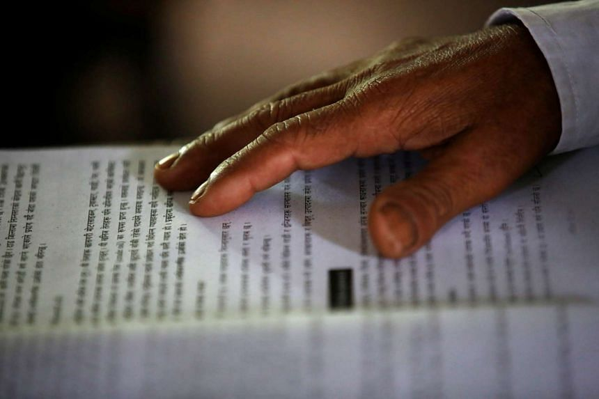 Durga Kami, 68, who is studying in the tenth grade at Shree Kala Bhairab Higher Secondary School, puts his hand on a book as he attends a class in Syangja, Nepal, on June 5, 2016.