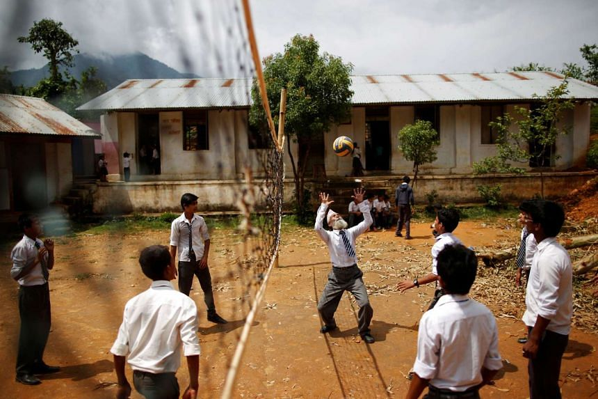 Durga Kami, 68, who is studying in the tenth grade at Shree Kala Bhairab Higher Secondary School, plays volleyball with friends during a break in Syangja, Nepal, on June 5, 2016.