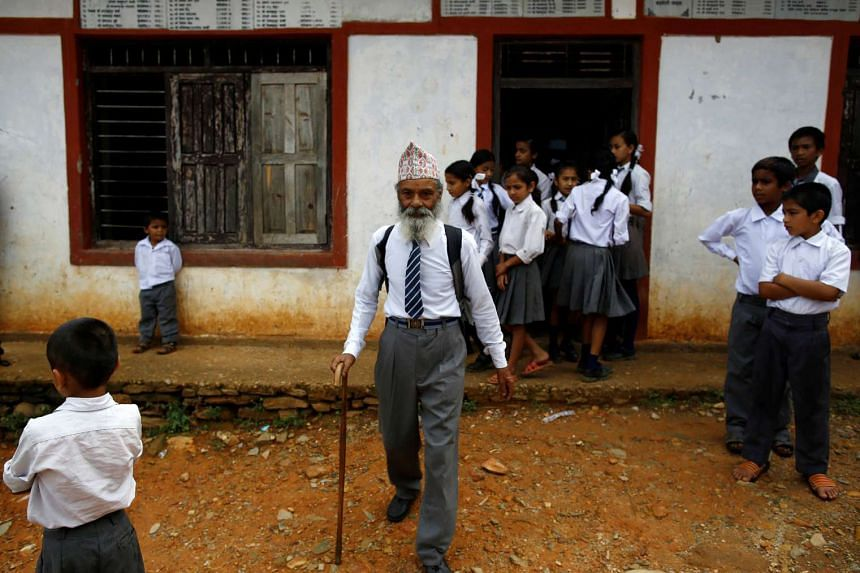 Durga Kami, 68, who is studying in the tenth grade at Shree Kala Bhairab Higher Secondary School, walks outside the school in Syangja, Nepal, on June 5, 2016.