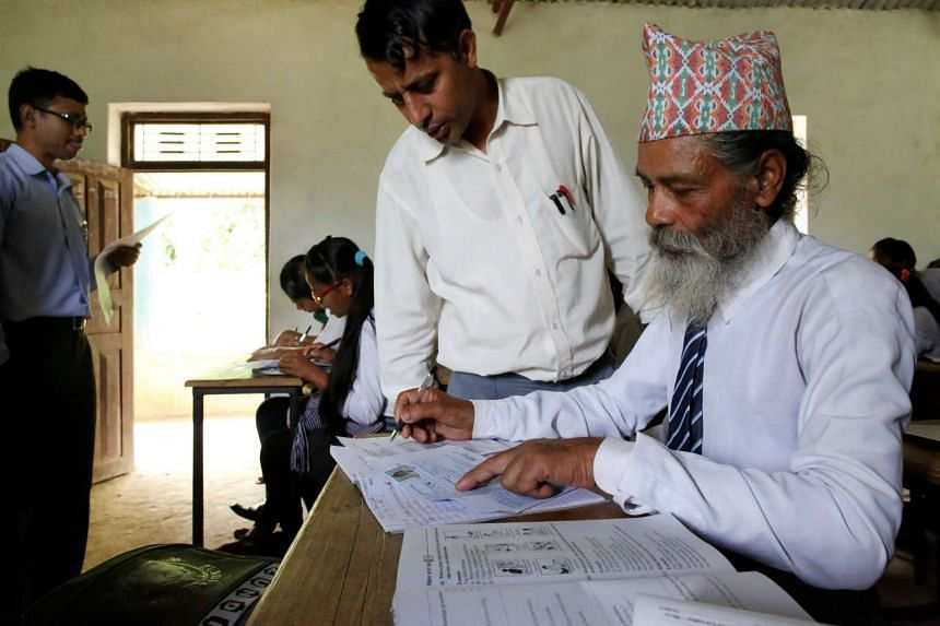 A teacher helps Durga Kami, 68, who is studying in the tenth grade at Shree Kala Bhairab Higher Secondary School, to fill his registration form to apply for the upcoming School Leavers Certificate Exams in Syangja, Nepal, on June 6, 2016.